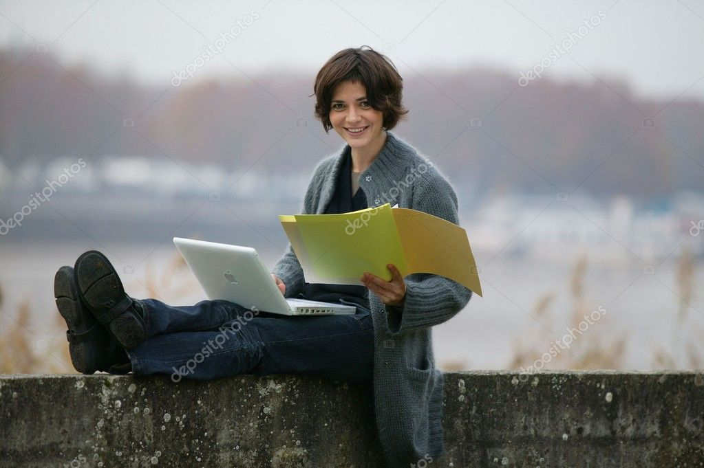 Woman studying whilst sat on a wall  Stock Photo #8954255