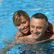 Couple swimming in hotel pool — Stock Photo #8960857