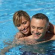 Stock Photo: Couple swimming in hotel pool