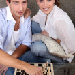 Young couple playing chess — Stockfoto