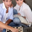 Young couple playing chess — Stock fotografie