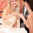 Girls drinking champagne in a restaurant — Stock Photo