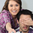 Young couple larking about with a games console - Stock Photo