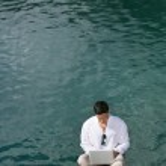hombre con ordenador portátil cerca de un lago — Foto de Stock