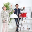 Man fitting ceiling light for old lady - Stock Photo