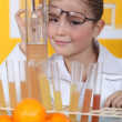 Little girl conducting experiment on oranges — Stock Photo #8961887