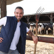 Farmer with a hayfork in front of cowshed - Stock Photo