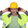 Builder with hard hat removing earmuffs — Stock Photo