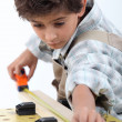 Foto Stock: Boy doing carpentry
