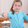 Child weighing flour on a scale — Stock Photo #8962501