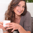 Young woman having a hot drink at home — Stock Photo
