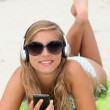 Girl listening to music on the beach — Stock Photo
