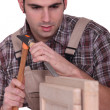 Man using hammer and chisel - Stock Photo