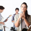 A guitar player, a drummer and a female singer — Stock Photo