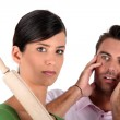 Angry woman threatening man with rolling pin — Stock Photo #8962828