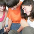 Three teenagers with smart phone — Stock Photo