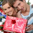 Young couple with a Christmas present — Stock Photo