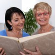 Two women looking through photo album — Stock Photo #8963191