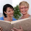 Two women looking through photo album - Stock Photo