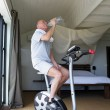 Man cycling on machine at home — Stock Photo #8963229