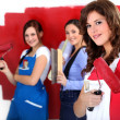 Three women painting a wall in red. — Stock Photo