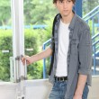 Male student opening door - Stockfoto