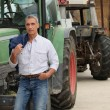 Farmer posing near tractors - Stock Photo