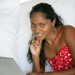 Beautiful Afro-American woman lying on the couch with her laptop — Stock Photo #8963546