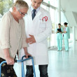 Doctor helping a patient with a walking frame — Stock Photo