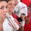 Sporty young girl drinking bottled water with other young sports in — Stock Photo