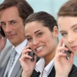 Three businesspeople on phone — Stockfoto