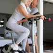 Middle-aged blonde woman on exercise bike coached by husband — Stock Photo