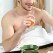 Man having breakfast in bed — Stockfoto