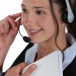 Smiling woman wearing a headset and holding a notebook - Stock Photo