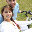 Young couple riding bikes in a park — Stock Photo #8963769