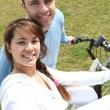 Young couple riding bikes in a park — Stock Photo