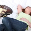 Girl with electric guitar in bedroom — Stock Photo