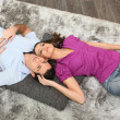 Stock Photo: Womcuddling mlaid on carpet