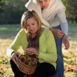Mother and daughter gathering chestnuts in garden - Stock Photo