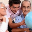 Grandparents ant their grandson looking at a globe - Foto Stock