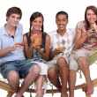 Friends drinking cocktails on a hammock - Stock Photo