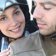 Smiling couple on a motorbike — Stock Photo