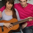 Stockfoto: Couple playing guitar at home