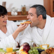 Playful couple having breakfast — Stock Photo