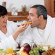 Playful couple having breakfast - Stock Photo