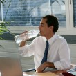 Businessman drinking from a large bottle of water — Stock Photo
