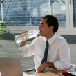 Stock Photo: Businessmdrinking from large bottle of water