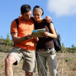 Stock Photo: Young couple walking through nature consulting map