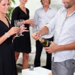 Friends popping the champagne — Stock Photo