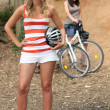 Stock Photo: Two young women reposing near mountain bikes